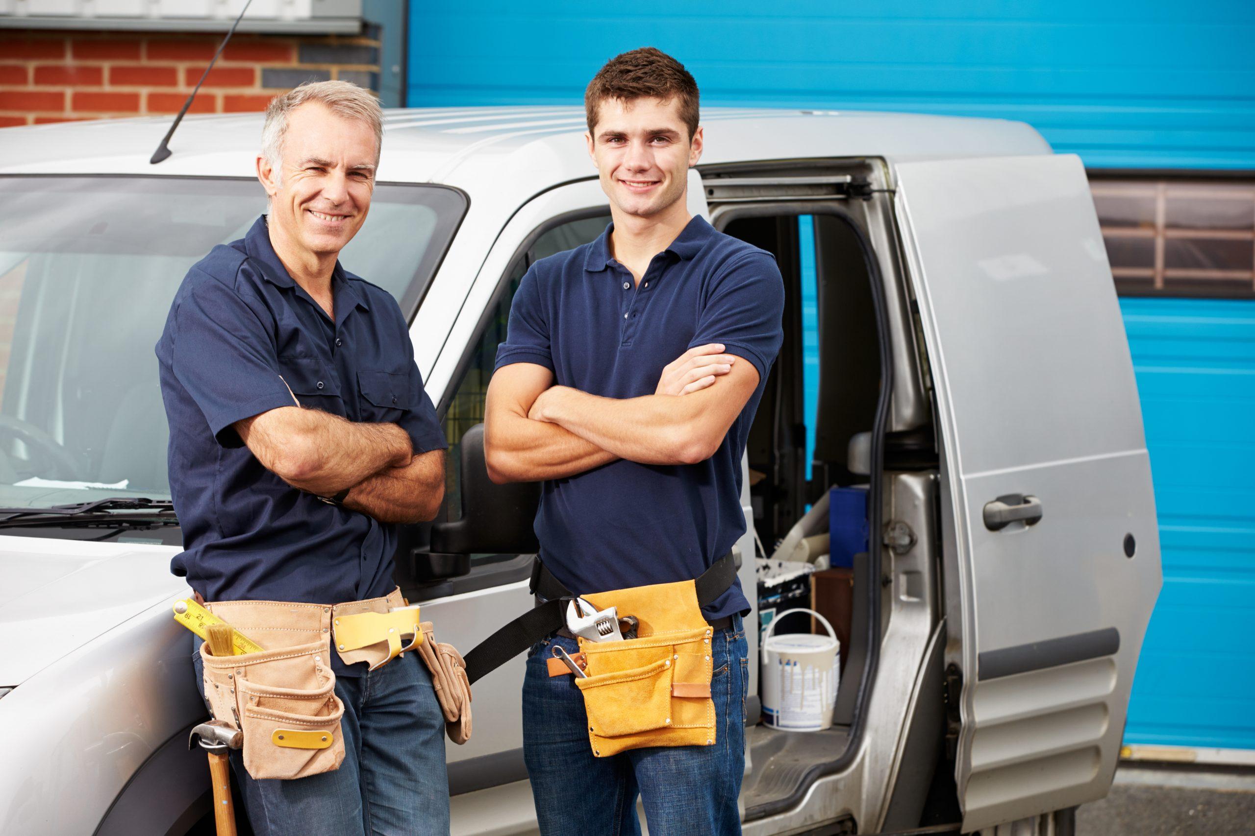 Zwei Handwerker eines Partnerunternehmens vor einem Auto